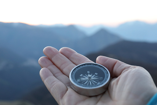 hand holding compass on mountain