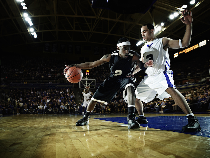 NCAA college basketball players dribbling down the court during a game