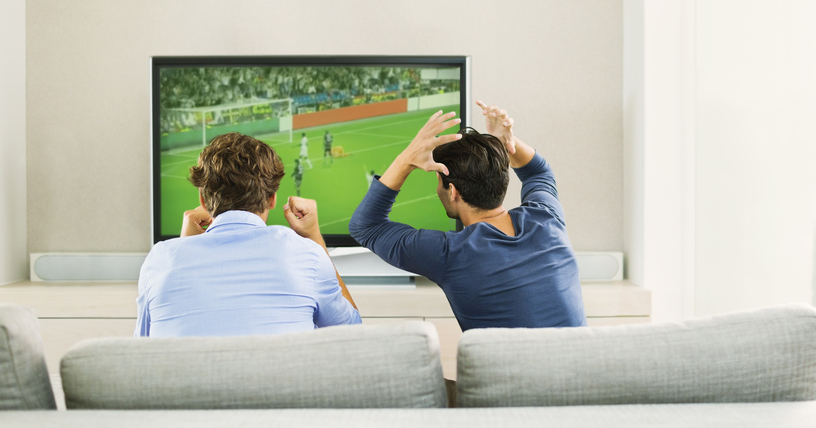 Men betting on sports and watching soccer game on sofa