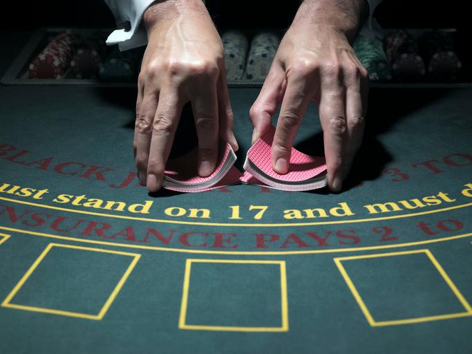 dealer shuffling cards at a blackjack table