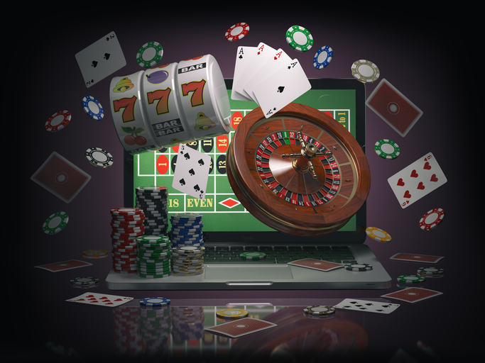 Online casino concept. Laptop roulette, slot machine, chips and cards