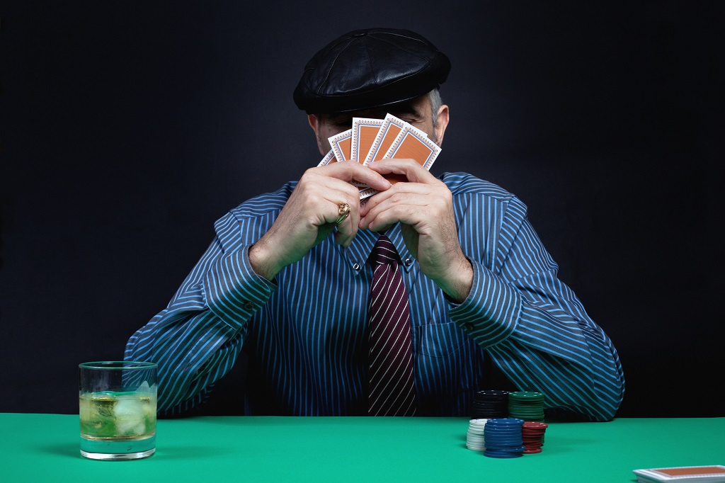 Poker player hiding his face with the cards.
