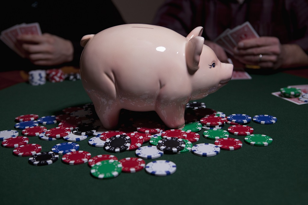 People playing poker with a piggy bank containing the winning prize in the middle of the poker table