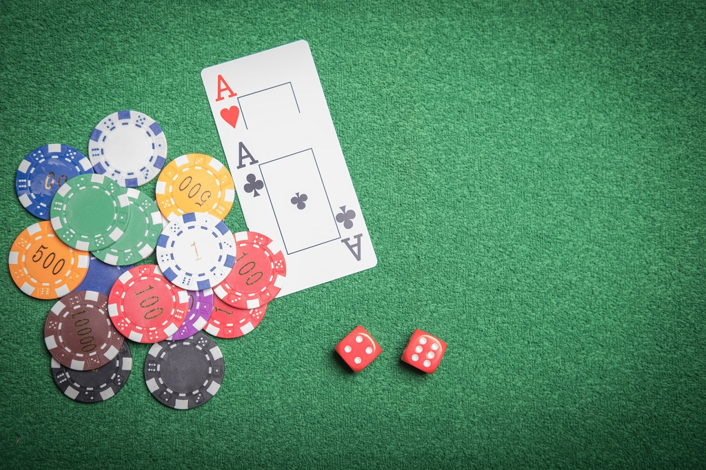 Pair of aces, dice and poker chips on the table during a game of Pot Limit Omaha