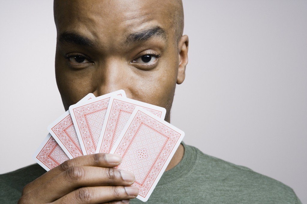 Poker player holding his cards in front of his face during a game