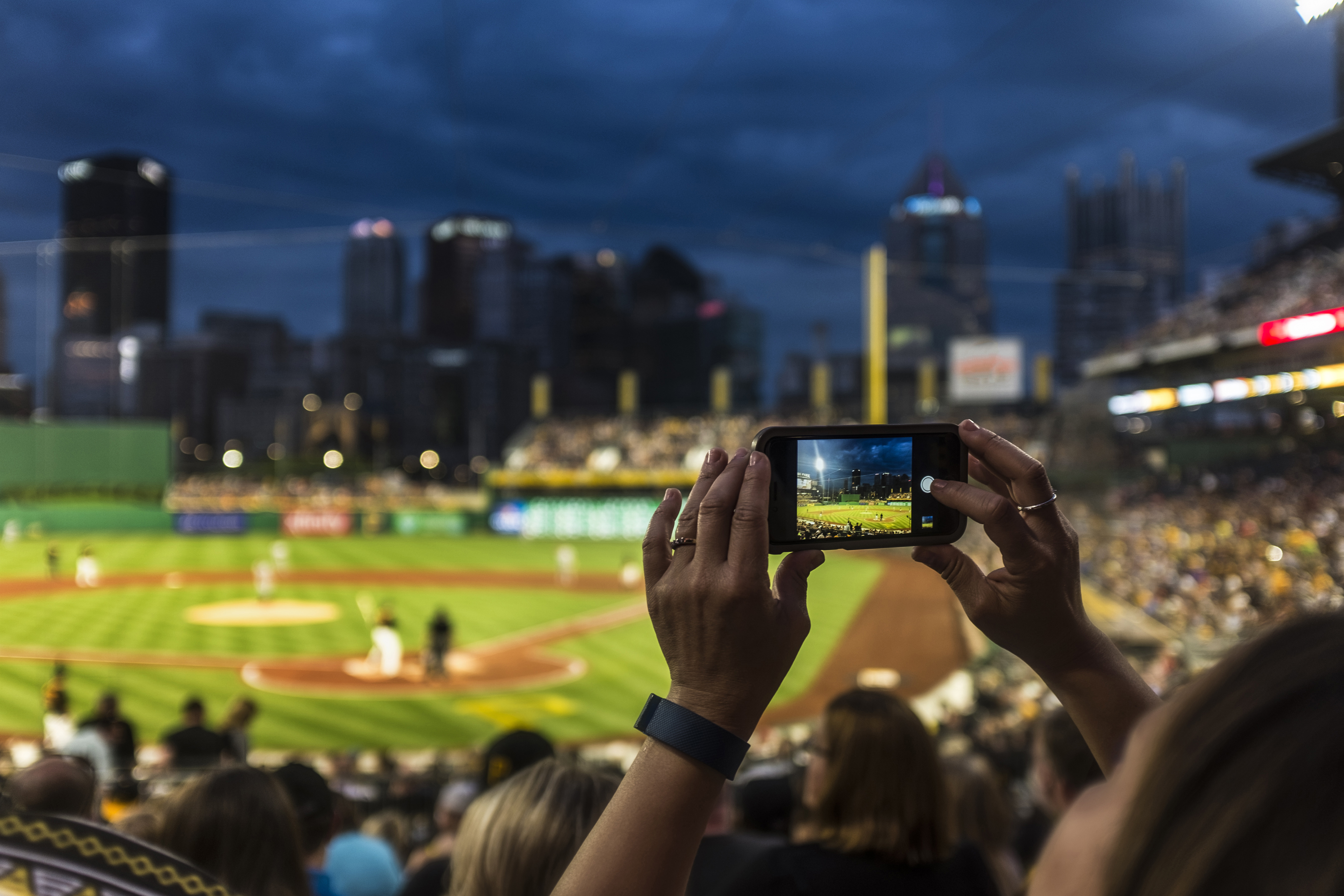 Woman taking a picture at a Pittsburgh Pirates baseball game at PNC Park in Pittsburgh, Pennsylvania