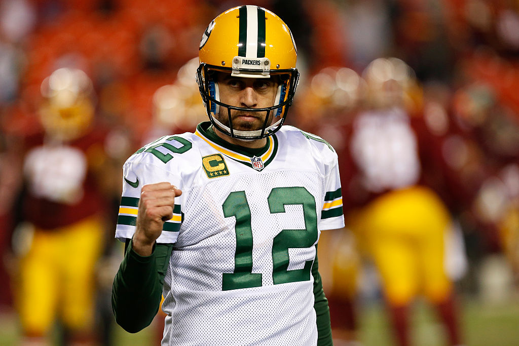 Aaron Rodgers in football uniform clenching his fist and looking to his right