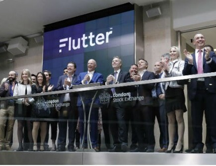 People standing in front of Flutter logo at London Stock Exchange