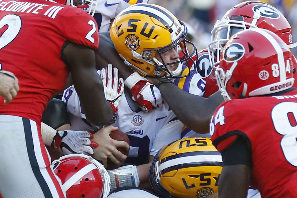 LSU Football player being tackled by Georgia Bulldogs players