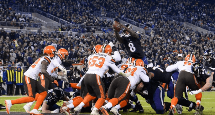 QB Lamar Jackson of the Baltimore Ravens leaps toward the end zone in football game