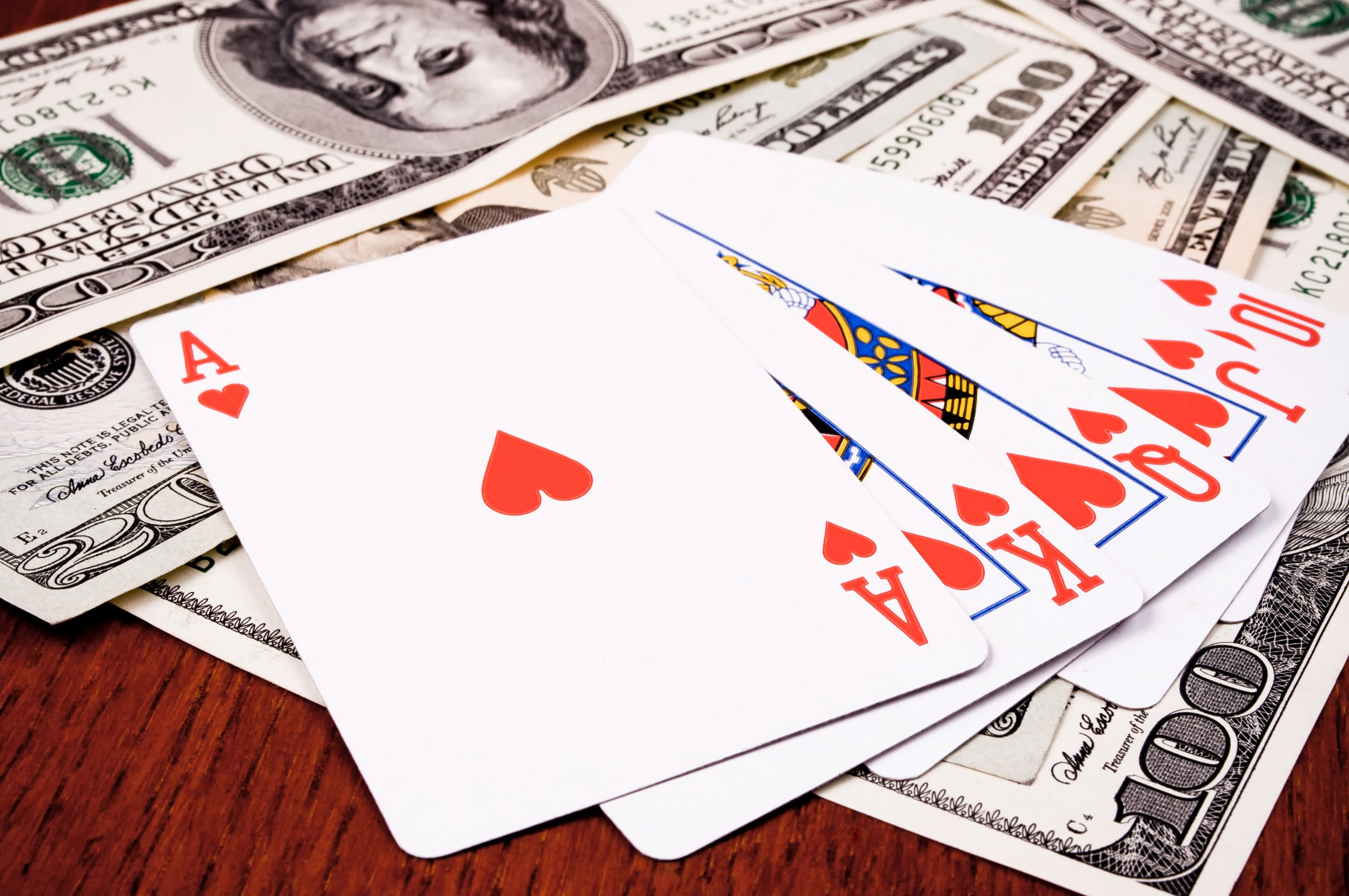 Royal flush with a bundle of cash on the table