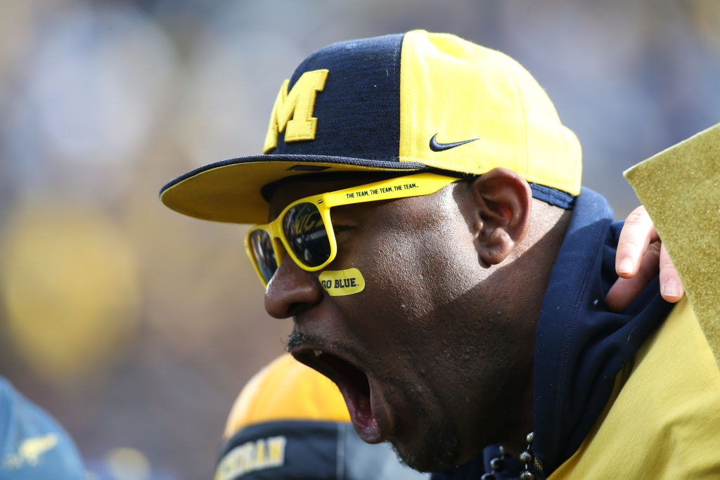 A Michigan fan cheers during a football game