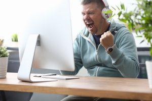 man yells at computer while winning online slot jackpot