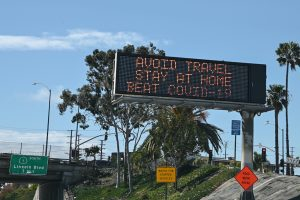 Highway sign saying 'avoid travel, stay at home, beat COVID-19'