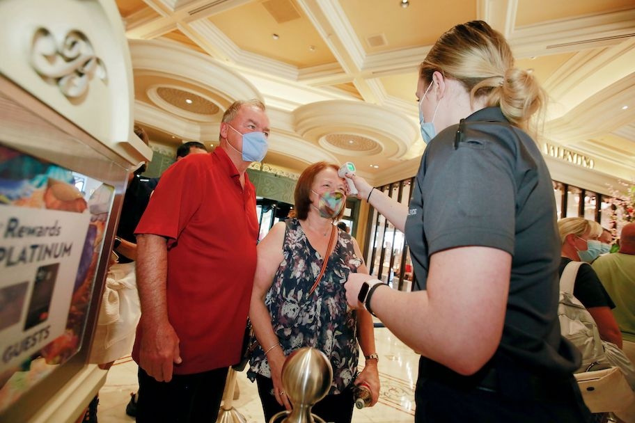 bellagio casino staffer takes guests temperatures as las vegas casinos reopen