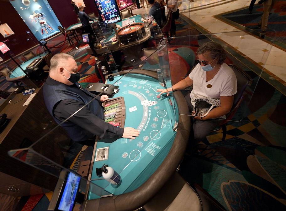 las vegas casino dealer and gambler wear face masks as they gamble in reopened las vegas casinos