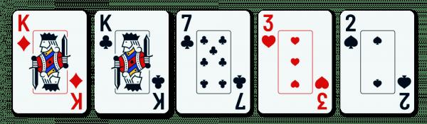 viisi pelikorttia, joiden joukossa on yksi pari (kuningas) ja kolme sivukorttia