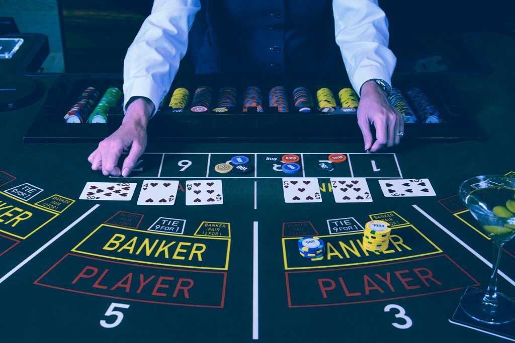 a dealer stands behind a baccarat table covered in cards and chips