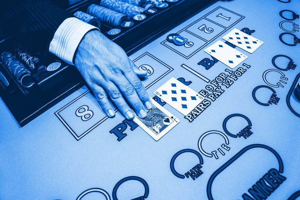 dealer laying out cards in a game of baccarat