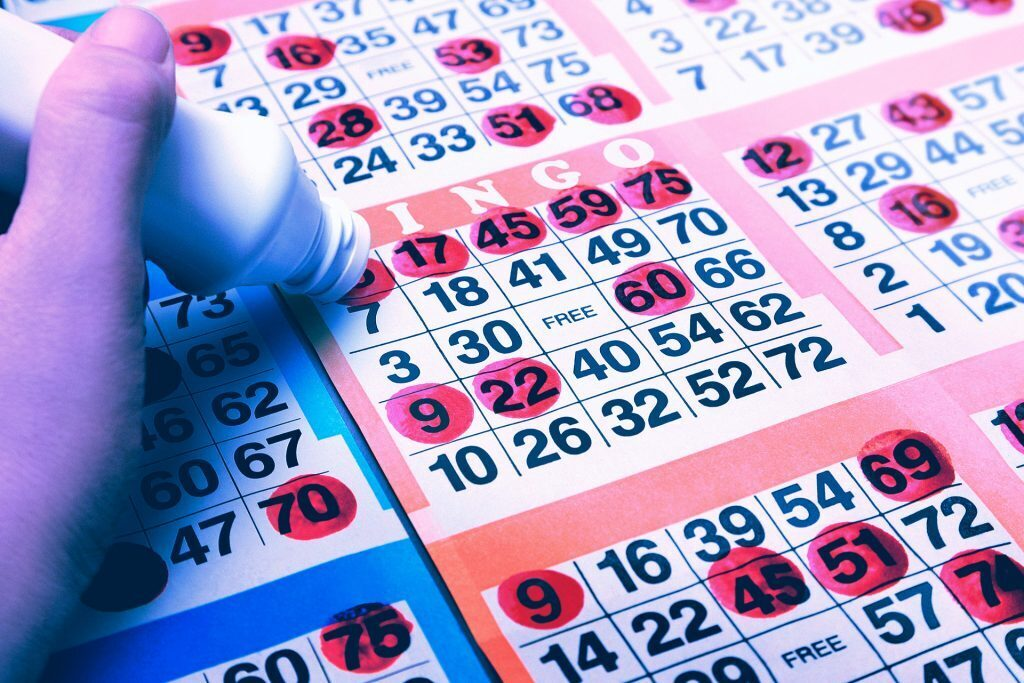 värikäs kuva bingolomakkeesta, johon käsi on merkitsemässä numeroita punaisella