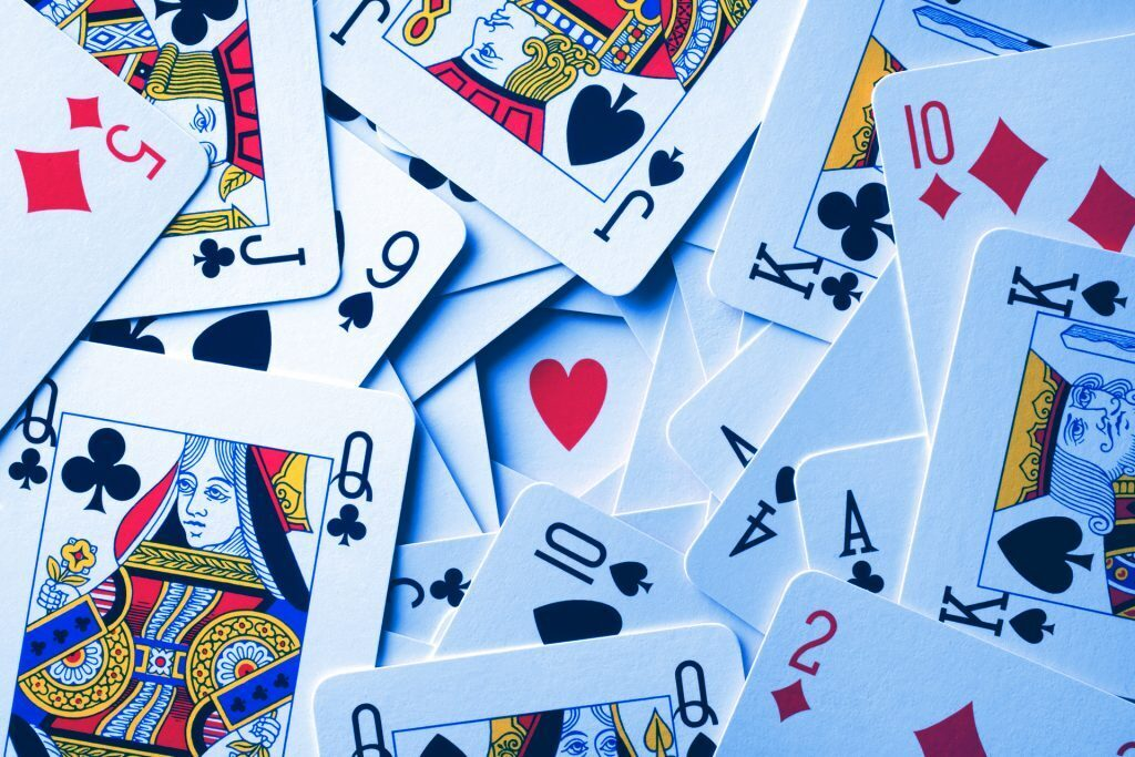 a pile of playing cards of different suits and values