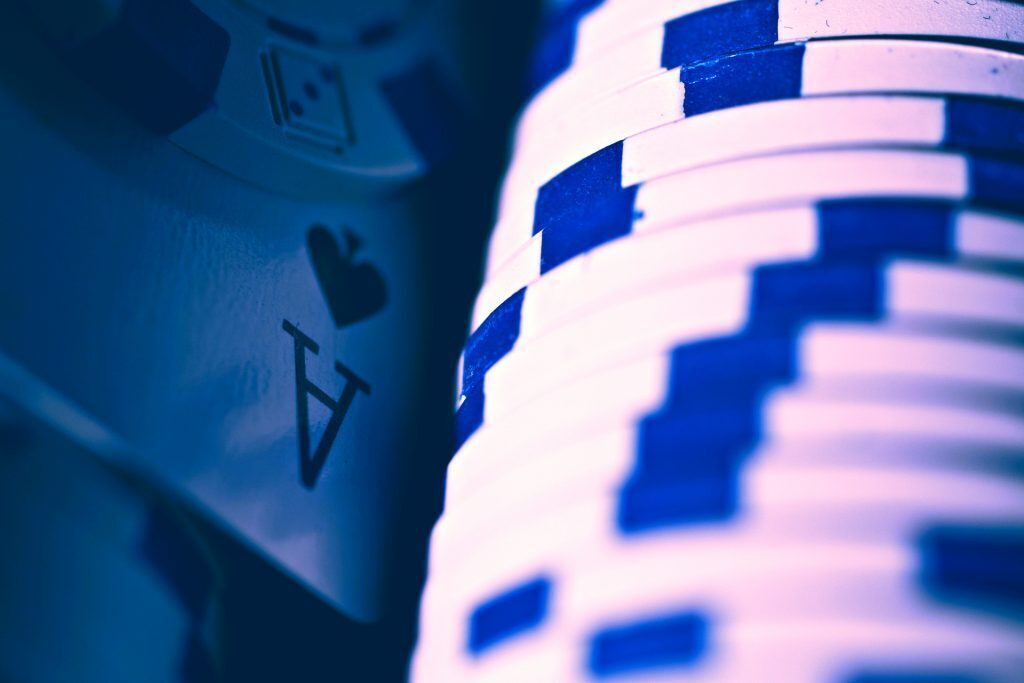 a stack of blue and white poker chips next to an ace of spades