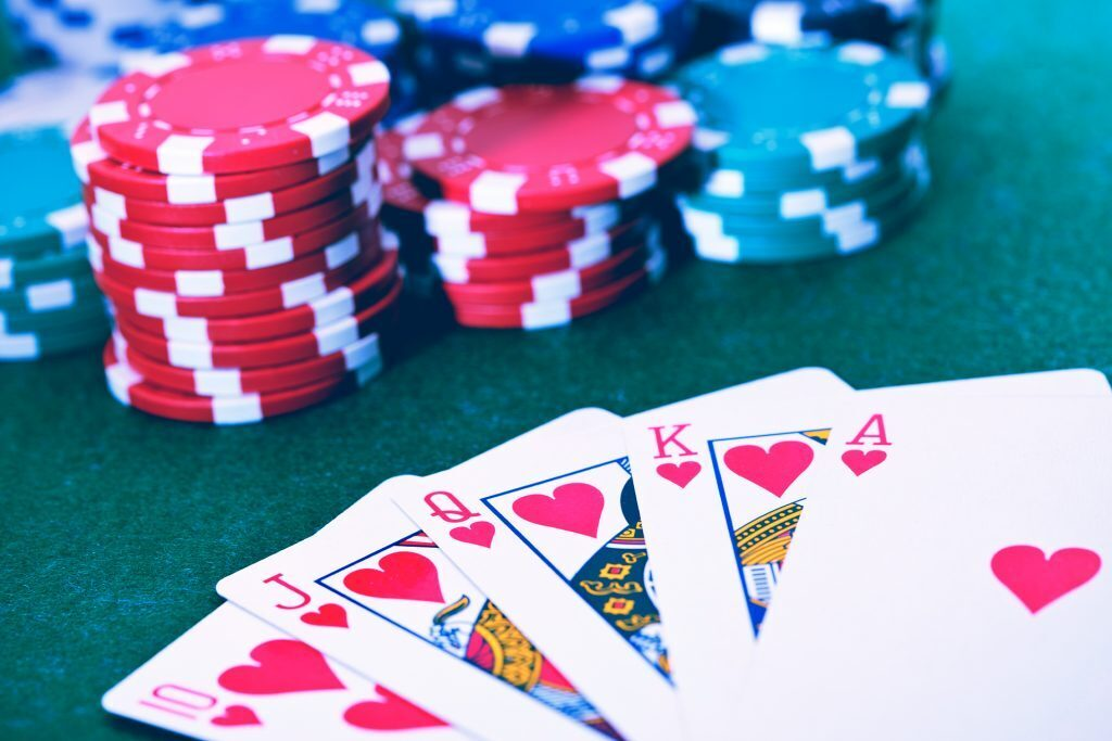 a royal flush - the 10, Jack, Queen, King, and Ace of Hearts - sit next to poker chips