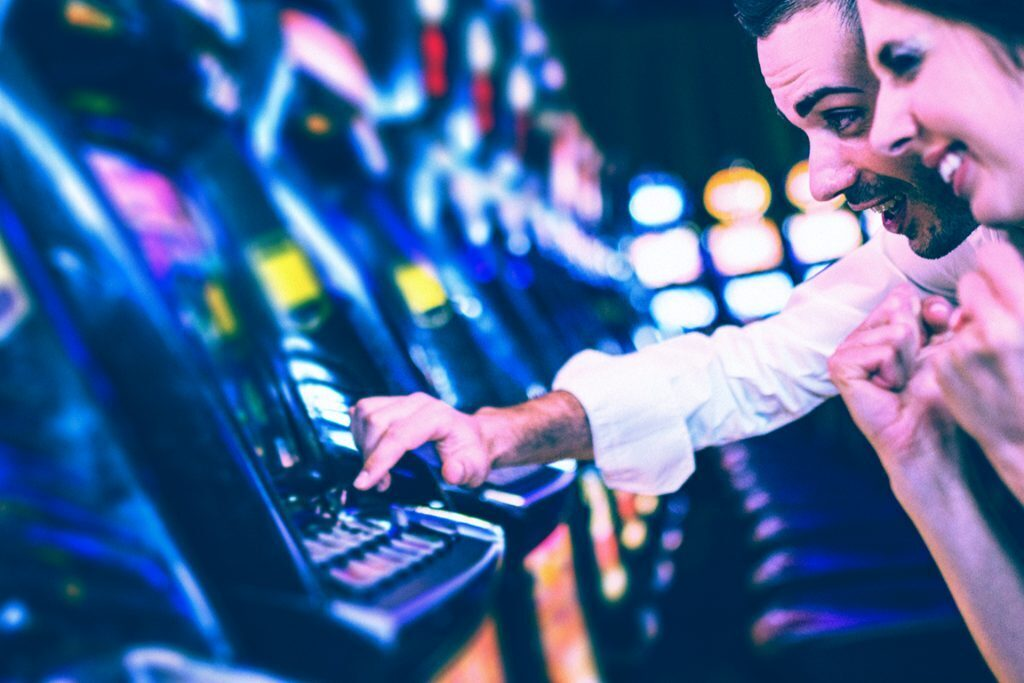 a man and woman play a slot machine
