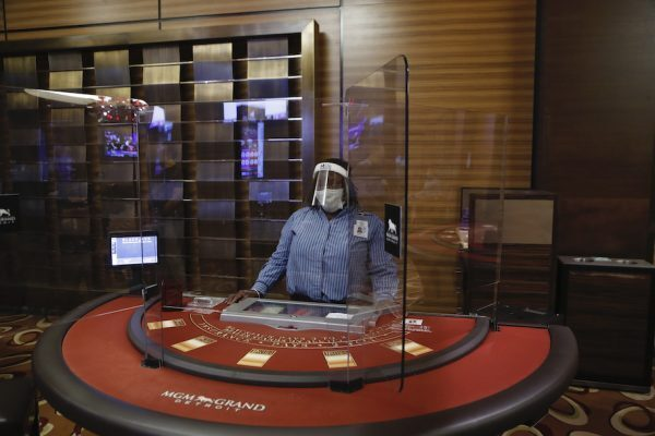 A masked dealer stands at an empty blackjack table with plexiglass dividers