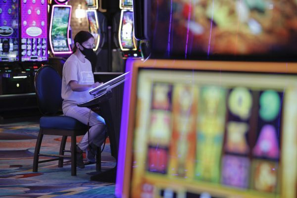 Sole masked player sits at a slot machine