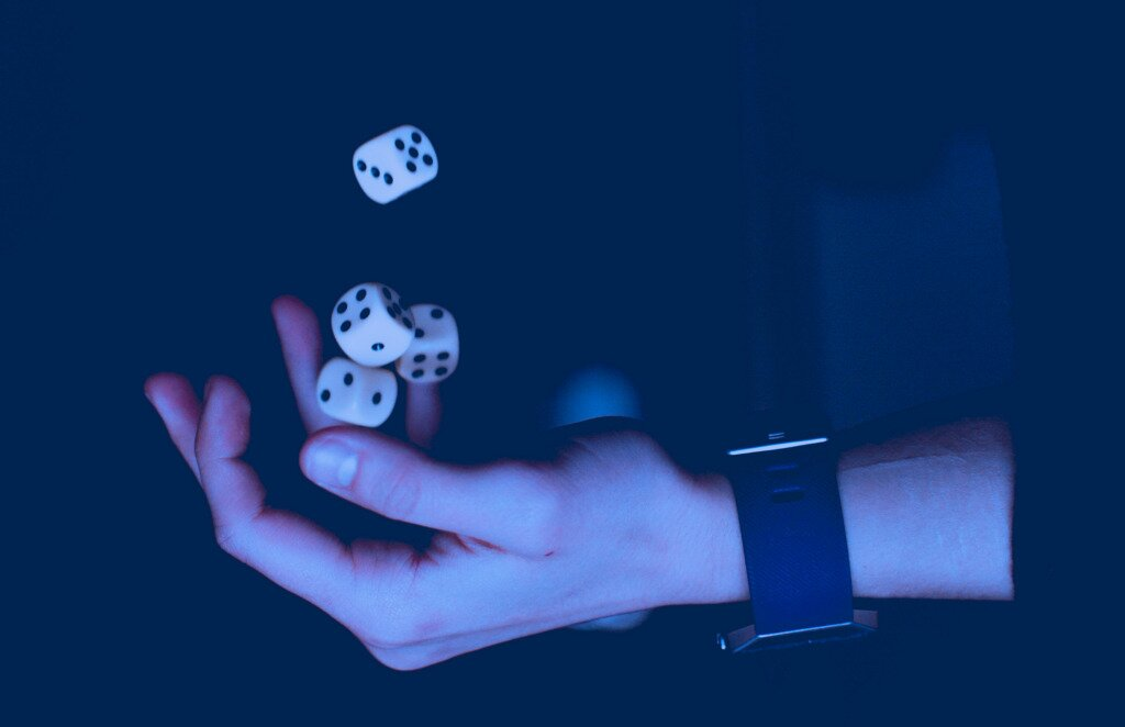 a hand throws four dice into the air