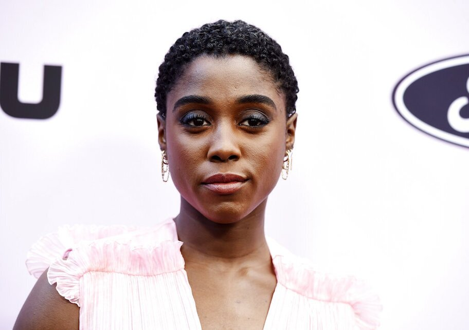 Lashana Lynch in white dress on red carpet