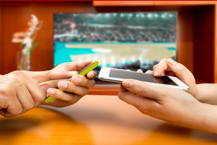 two people bet on sports from phones with game playing in background