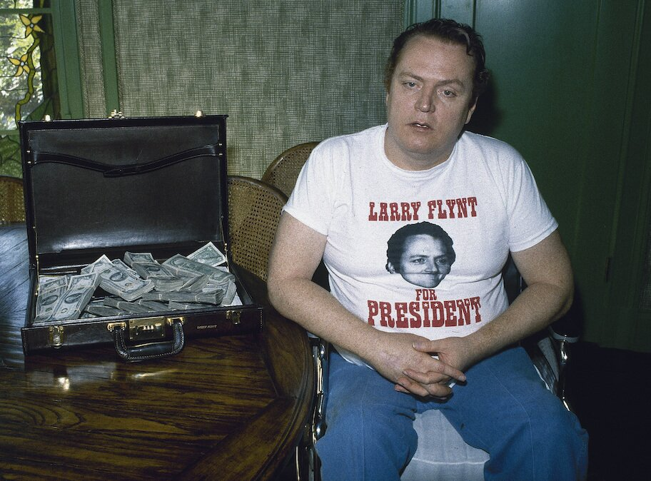 larry flynt with suitcase of cash and larry for president shirt