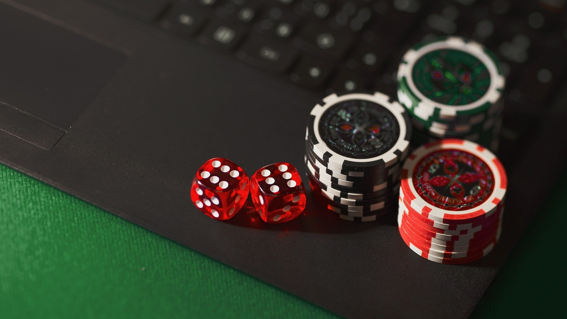 poker chips and dice on laptop