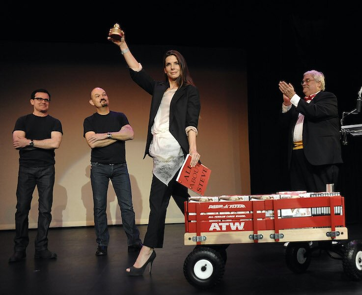 sandra bullock razzie awards handing out her movie in wagon on stage