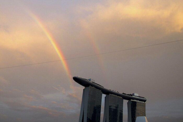marina bay sands hotel tower with rainbow and sunset in background