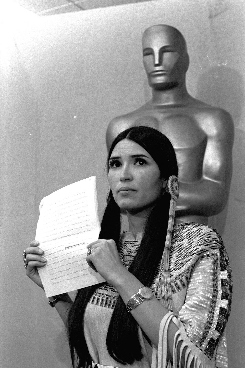 Sacheen Littlefeather 1973 oscars for marlon brando holding speech standing in front of oscar statue