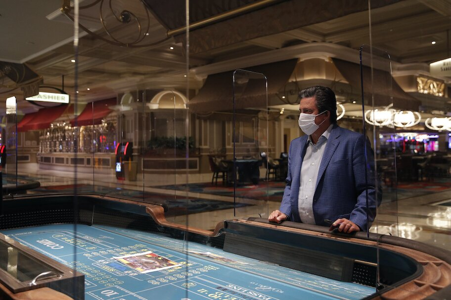 mgm ceo bill hornbuckle stands behind covid partition at blackjack table