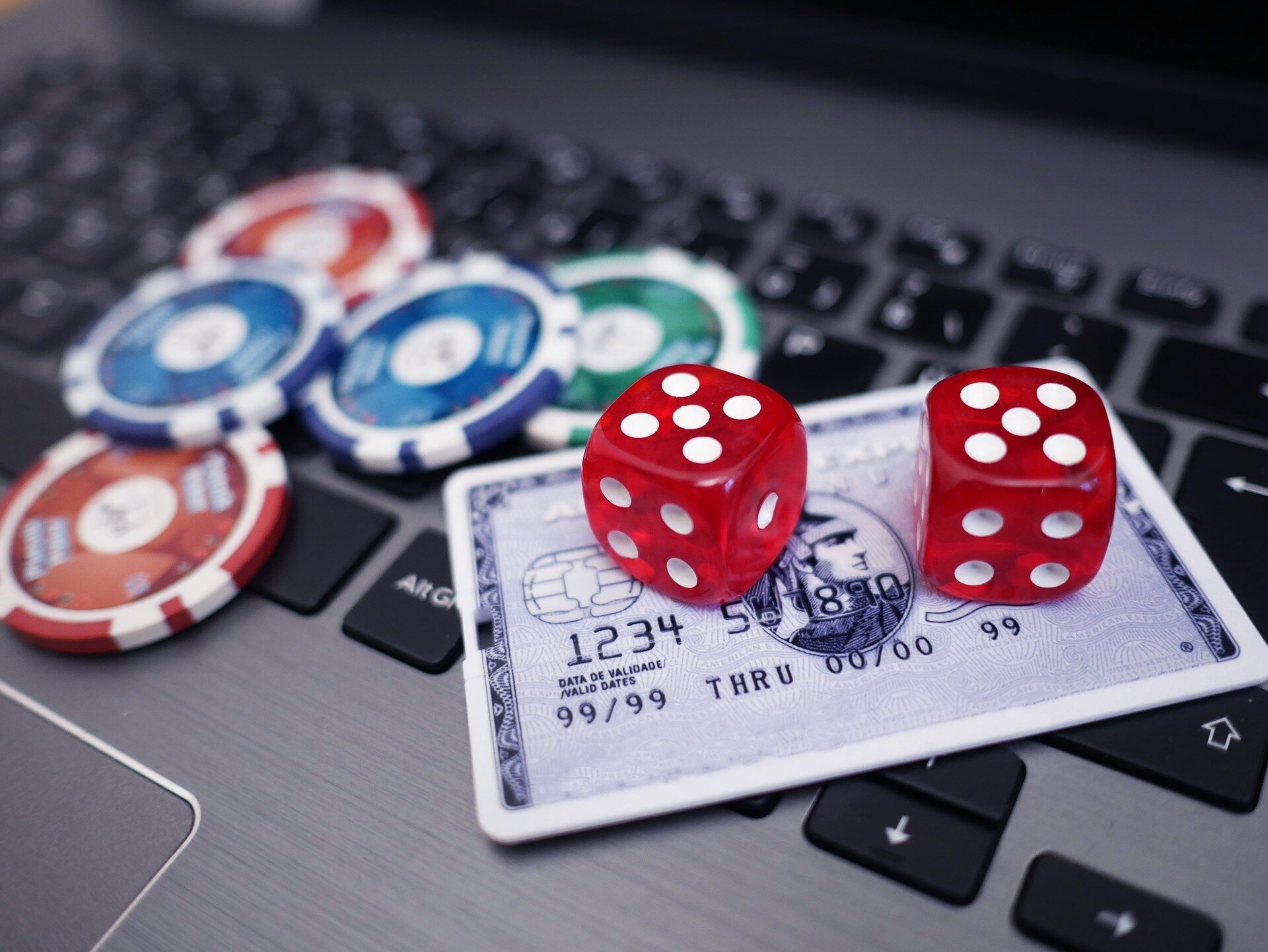 credit card, poker chips and playing cards on laptop
