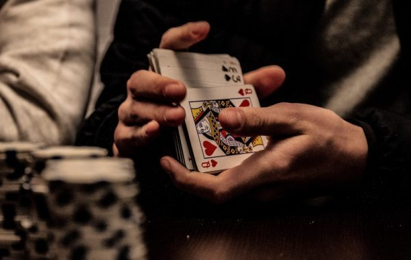 person shuffling deck of cards at poker table