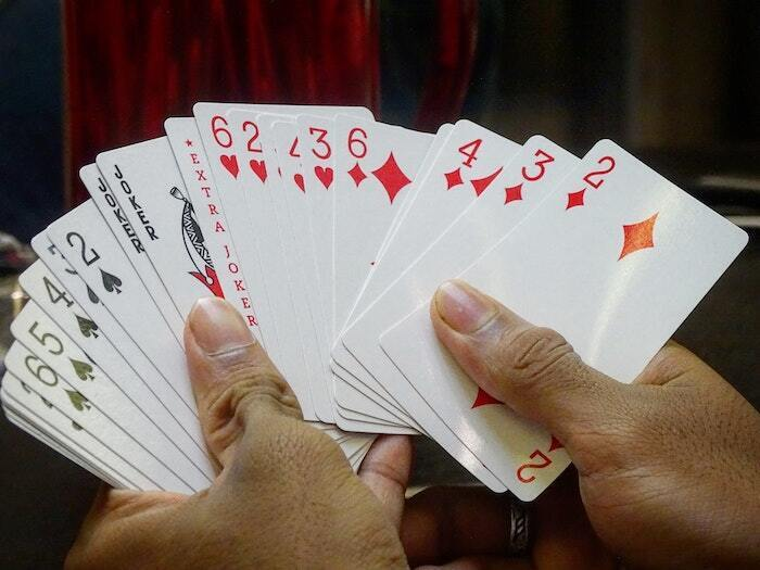 man holding playing cards during texas holdem poker