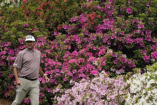 Bubba Watson walks by azaleas at the Masters
