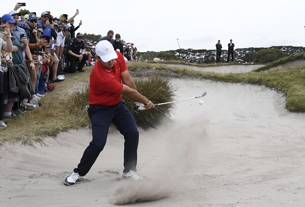 Patrick Reed hits a shot out of the bunker