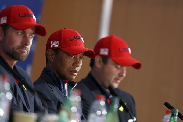 Tiger Woods and Patrick Reed listen to a question