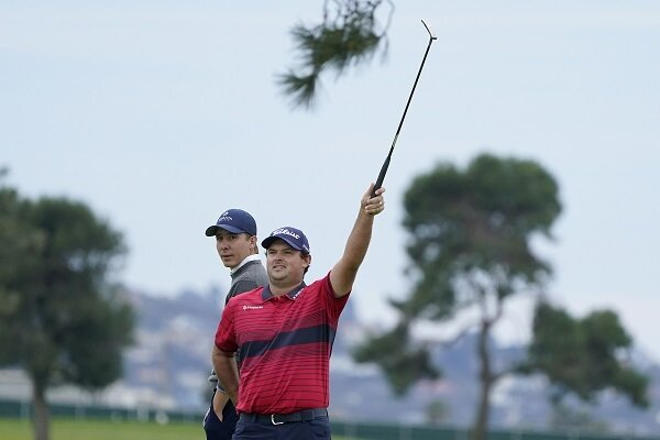 Patrick Reed signals for an official