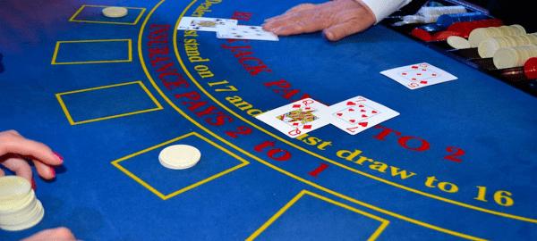 casino dealer at blue felt table dealing card