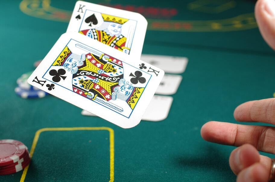 two cards leaving hand at felt casino table