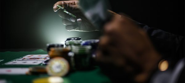 person playing poker hand and betting with chips stacked