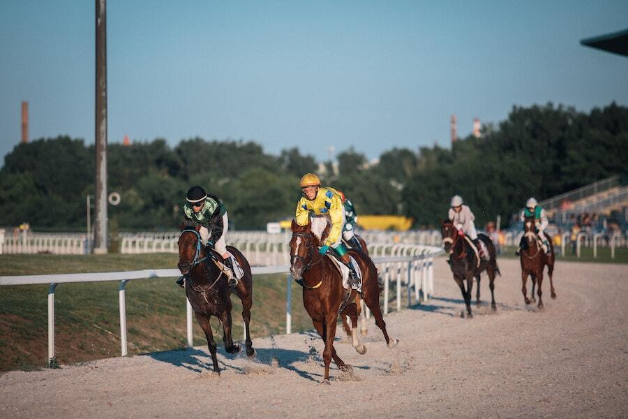 horses racing around track at horse race